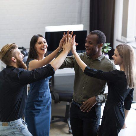 Group of young colleagues giving each other a high five while standing in an office